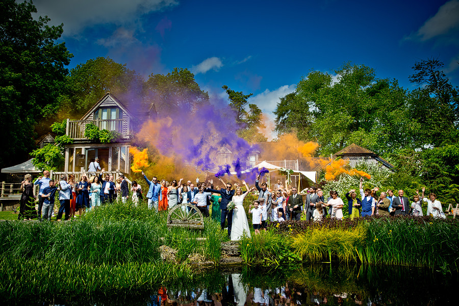 Everyone setting off colourful flares for a groups shot photo at wedding